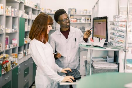 Team of two young apothecaries in pharmacy standing in front of shelves with drugs and working on computer making order of medicines