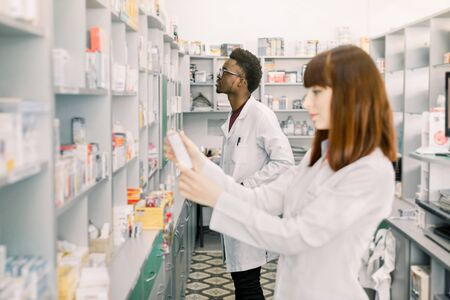 Two young multiethnical Pharmacists Working at modern pharmacy. Female Pharmacist Holding package with Pills, male pharmacist standing on the background. Pharmacists Wearing Medical Uniform.