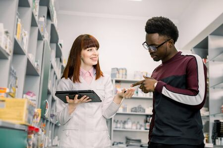 Young African man client is asking pretty woman pharmacist about medicines in apothecary