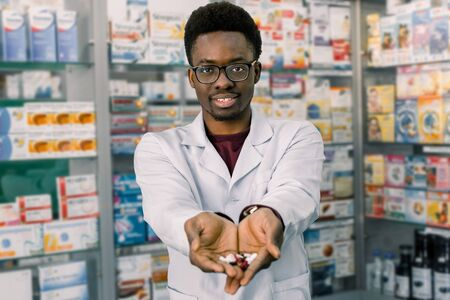 African-american pharmacist man holding tablets pills in the hands. Mans hands holding a handful of medicine pills, to treat diseases