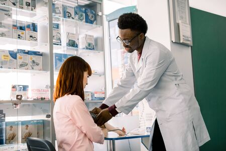 Blood pressure measuring. African man Pharmacist or Doctor and young woman patient. Modern pharmacy background. Health care