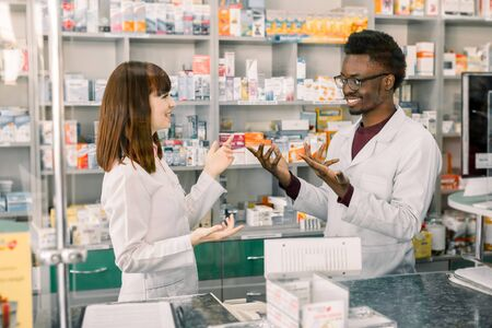 Portrait of multiethnical male and female pharmacists standing near pharmacy counter, talking, laughing and gesturing each other