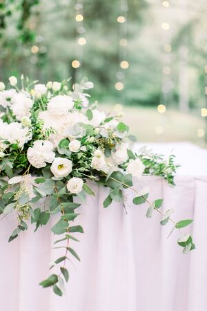 table setting with flower and greenery decoration, covered with tablecloth, outdoors in the garden or forest, small liths bulbs on the blurred background.