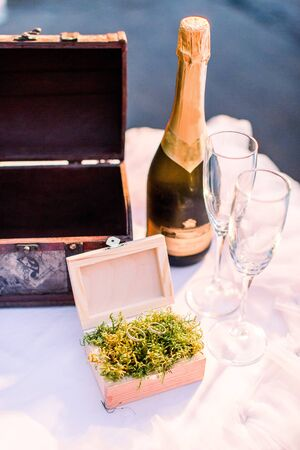 Vintage brown box for wedding wishes and little wooden box with wedding rings filled with green moss on the table. Bottle of champagne and two glasses. Wedding ceremony, rustic style