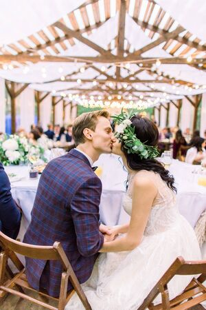 Bride and groom sitting at the table and kissing, with guests at wedding reception outside in the wooden tent restaurant in the forest. Rustic wedding outdoors Reklamní fotografie - 133211409