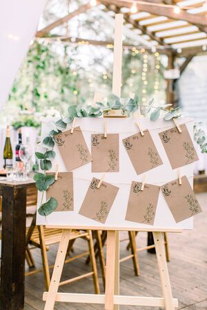 Decorated seating plan for wedding guests in woodent tent restaurant outdoors. Original rustic wooden board with guest list Imagens