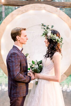 girl in a white wedding dress with bouquet and wreath on the head and man in suit are standing near the ceremonial wooden arch on a background of forest or garden outdoors