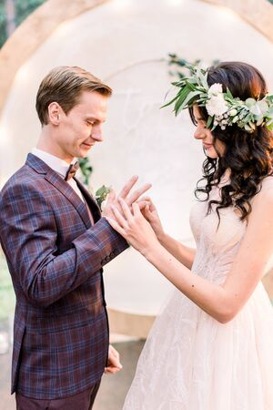 Wedding couple exchange rings on wedding ceremony outdoors. Bride with a bouquet of flowers and greenery and groom in elegant suit with arch on background, rustic style Stock Photo
