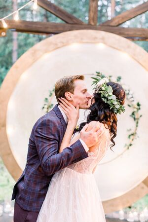 The newlywed stylish couple is hugging and kissing near the wedding arch in the restaurant in rustic style outdoors. Reklamní fotografie - 133211452