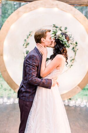 The newlywed stylish couple is hugging and kissing near the wedding arch in the restaurant in rustic style outdoors.