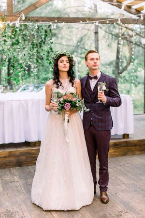 Stylish bride and groom with glasses of champagne are standing in wooden tent restaurant in forest outdoors. Rustic wedding ceremony outdoors. Happy newlyweds. Full length portrait