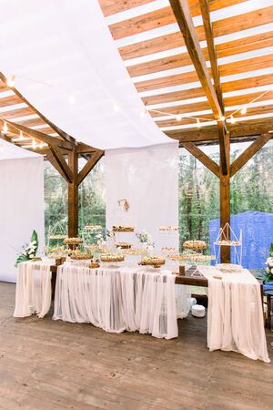 Wedding stand-up meal. Snack for guests. Celebration. Wedding buffet in restaurant outdoors, wooden tent. Catering