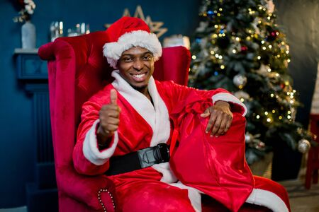 Christmas and Happy New Year concept. Smiling African male santa claus holding a red sack with Christmas gifts while sitting on a red chair near the Christmas tree. Stok Fotoğraf