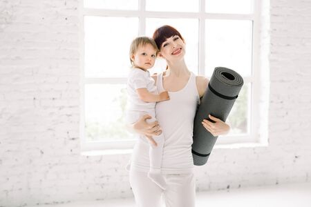 Portrait of beautiful young mom in white sports wear holding her charming little baby girl and yoga mat, looking at camera and smiling while standing against window in light big hall.