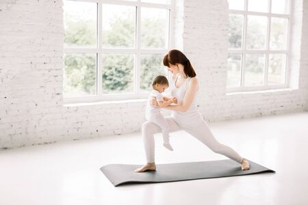 Young mother doing yoga with her little baby at big light gym hall, standing against big windows.