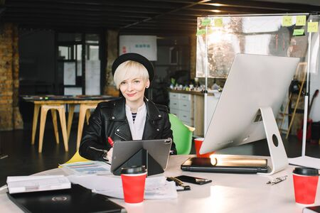 Young woman architect in black hat and leasure jacket working at the table. Photo of blond woman working with new startup project in modern loft