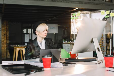 Concentrated young beautiful blond businesswoman in casual wear working on PC and tablet in bright loft modern office.