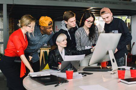 El trabajo en equipo y la formación de equipos es un éxito. Socios de puesta en marcha ocupados que trabajan con computadoras y tabletas, con ropa informal, tan concentrados, discutiendo las ideas para una nueva estrategia de desarrollo en una oficina agradable.