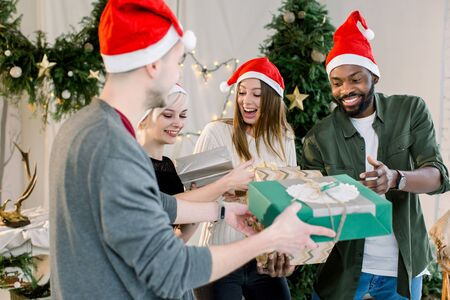 Cheerful young four international people celebrate Christmas and New Year together in cozy decorated studio. Group of friends laughing and sharing Christmas gifts. Stok Fotoğraf