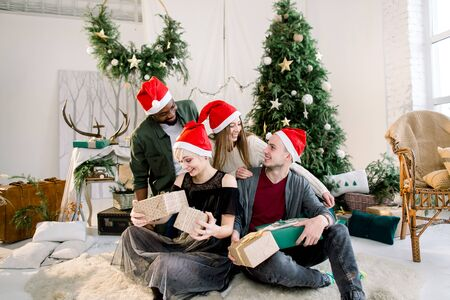 Cheerful young four international people celebrate Christmas and New Year together in cozy decorated studio