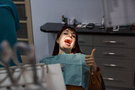 Smiling young woman showing thumb up is ready for dental treatment sitting in the dental office. Smiling and happy young woman after successful treatment without pain. Stok Fotoğraf