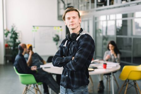 Young Caucasian freelancer with smile on his face and earphones standing in coworking place loft office while his colleagues sitting at the table and having meeting about startup.