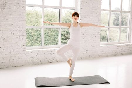Young sporty woman practicing yoga at home, standing in Vrksasana exercise, Tree pose, working out, wearing white sportswear, indoor full length, window background. Stok Fotoğraf