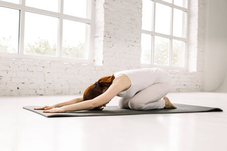 Yoga, fitness, sport, training and lifestyle concept - smiling woman in white sportswear stretching body on mat in gym. Stok Fotoğraf