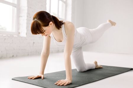 Young yogi attractive woman practicing yoga concept, standing in Donkey, Kick fire hydrant exercise, working out, wearing white sportswear, white loft background.