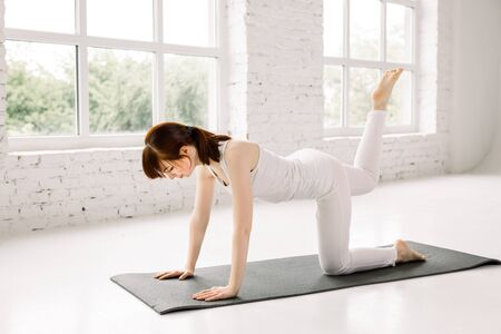 Yoga, fitness, sport, training and lifestyle concept - smiling young woman training leg on mat in gym. Woman practicing yoga, doing Donkey Kick exercise, working out, wearing sportswear, yoga studio.