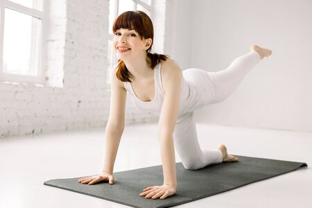 Bodyweight exercises - fitness woman doing fire hydrants legs kickbacks. Active girl training glute muscles raising one leg to the side and back for strength training in indoor gym. Stok Fotoğraf