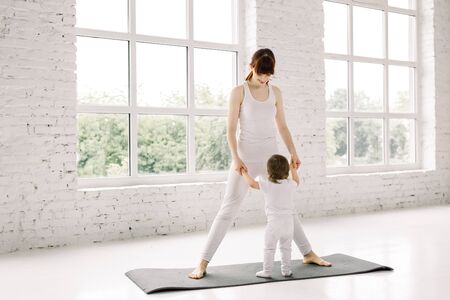 young mother does physical yoga exercises together with her baby, mother and little child holding hands, standing on the yoga mat in white loft yoga studio.