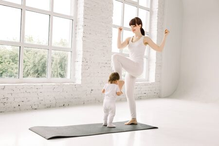 sports mother is engaged in fitness and yoga with her baby at fitness or yoga studio. Young sporty woman doing standing bicycle crunches together with baby. Stok Fotoğraf