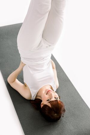 Yoga, fitness, sport, training and lifestyle concept - smiling woman doing sport exercise on mat in gym. Top view of woman exercising on yoga mat. Fitness female lying on exercise mat at gym