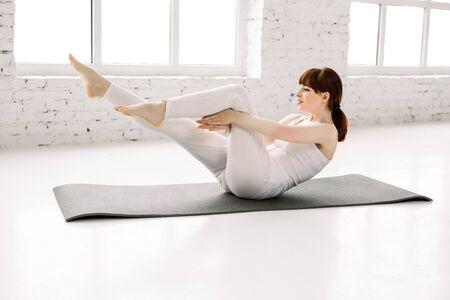 Young sporty woman practicing in gym, doing crisscross exercise, clapping crunches pose, working out, wearing white sportswear, indoor full length, yoga or fitness club. Stok Fotoğraf