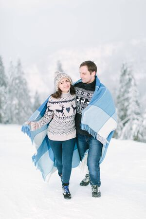 Family, love, holiday concept. Winter love in forest. Young couple walking in snowy forest, hugging and smiling, holding warm chekered blanket