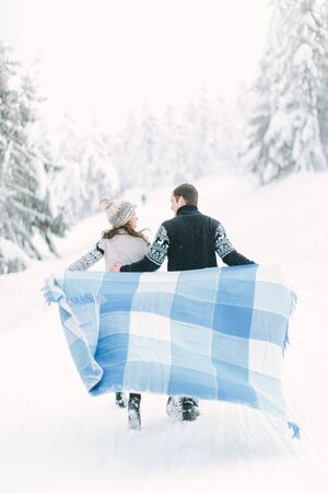 Young couple in love having a walk in winter snowy forest and holding warm wool blanket in hands