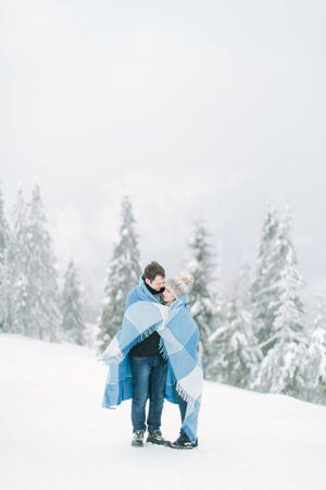 Young handsome man hugs his pretty young girl and covers her with the wool chekered blue blanket. Winter walk in snowy forest. Love in winter