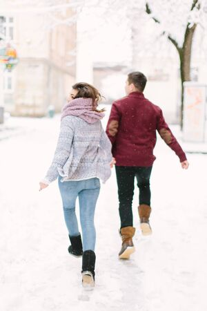 Winter city love. Happy young couple in warm sweaters having fun in winter city. Winter morning, christmas and holiday concept.