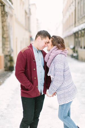 beautiful young couple in winter sweaters hugs and enjoys the winter morning in the city Stok Fotoğraf