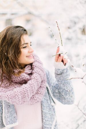 Beautiful happy young woman in a vintage fashion blue sweater and warm scarf walking in the winter city, standing near the tree with snow. Winter holiday and Christmas concept Stok Fotoğraf
