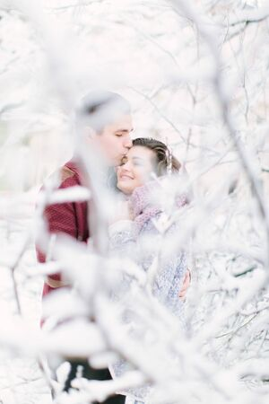 holidays, winter, christmas, hot drinks and people concept - happy couple in warm clothes hugging near the tree branches with snow
