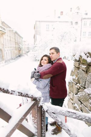 Winter city love. Happy young couple in warm sweaters hugging near the building in winter city. Winter morning, christmas and holiday concept.
