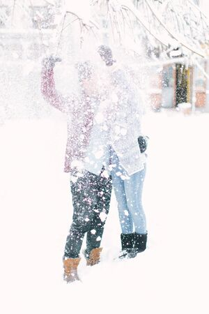 Young couple hugging and kissing in the city center in winter. Family, love, Christmas concept. Lviv, Ukraine Stok Fotoğraf