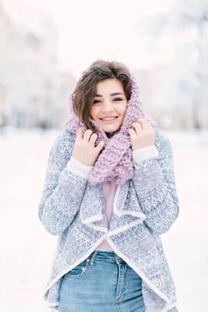 Happy winter time in big city of charming girl walking on street in warm sweater. Enjoying snowfall, expressing positivity, smiling to camera, joyful cheerful mood, true emotions, new year mood Stok Fotoğraf