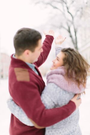Stylish young couple walking on european winter streets , have fun and hugging. Wearing trendy season outfit. Creamy warm colors.