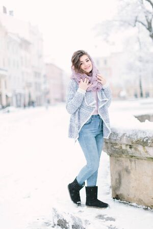 Happy winter time in big city of charming girl walking on street in warm knitted sweater. Enjoying snowfall, expressing positivity, smiling to camera, new year mood