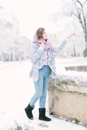 Beautiful happy young woman in a vintage fashion blue sweater and warm scarf walking in the winter city. Winter holiday and Christmas concept