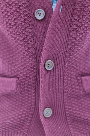 Stylish knitted burgundy sweater with buttons.