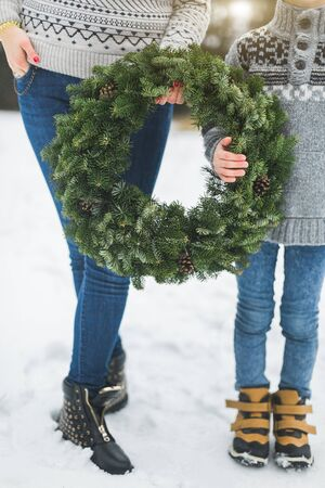 Cropped image of legs of mother and son, holding together beautiful Christmas wreath, standing outdoors in winter park or forest. Mother and child with Christmas wreath, outdoors.